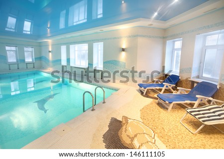 Beautiful clean pool with images of dolphins at bottom and sunbeds in big room. - stock photo