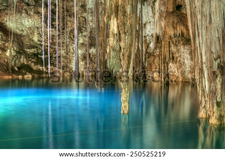 Beautiful clear blue water of Xkenken cenote in Dzitnup, Mexico illuminated from above with tree roots and stalactites hanging from ceiling of cavern - stock photo