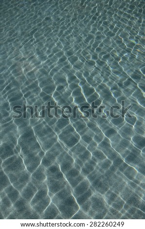 beautiful clear pool water reflecting in the sun background  - stock photo