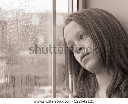 Beautiful close-up of a young girl gazing out of a window on a rainy day - stock photo