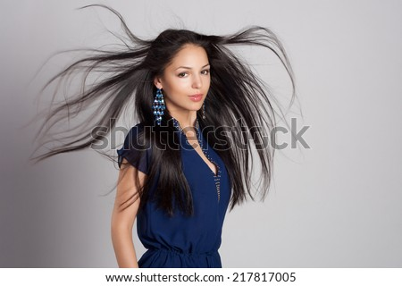 Beautiful close-up portrait of a young woman with healthy long windy hair. Blue dress and jewelry. Fashion shot. - stock photo