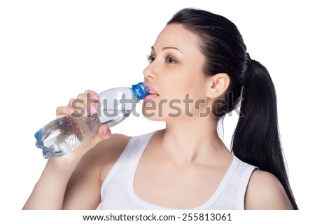 Beautiful close-up portrait of young woman with a bottle of water. Healthy drink and sport concept. Skin care and beauty. Sports.