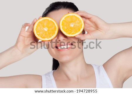 Beautiful close-up portrait of young woman with oranges. Healthy food concept. Skin care and beauty. Vitamins and minerals.