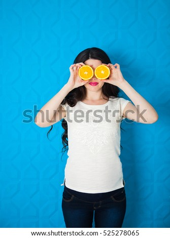 Beautiful close-up young pregnant woman with oranges. Healthy food concept. Skin care and beauty. Vitamins and minerals