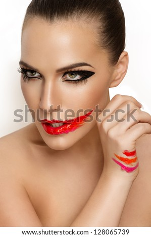 Beautiful closeup portrait of young caucasian female, red smeared lips, swatch on hand, perfect skin