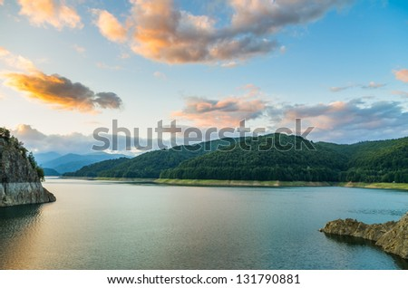 beautiful clouds at sunset over mountain lake - stock photo