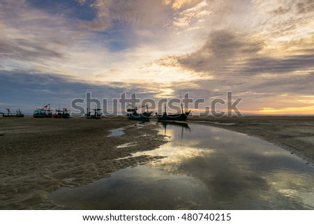 beautiful clouds in the morning at the beach with fishing boats
