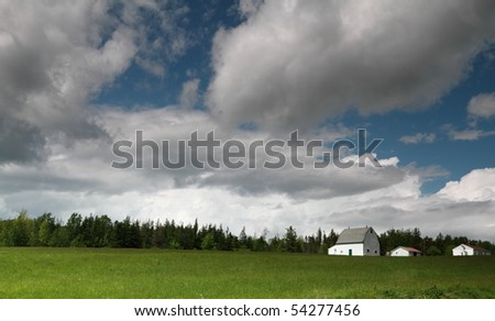 Beautiful clouds over an early summer hay field. - stock photo