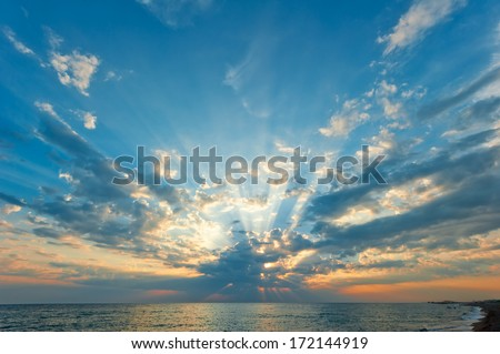 beautiful clouds with the setting sun over the sea - stock photo