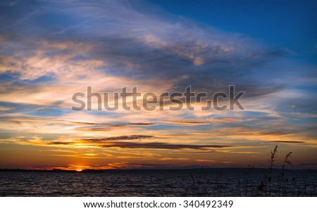 Beautiful cloudscape with sunset on a coast river - stock photo