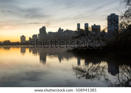 Beautiful cloudy sunrise at a lake in Stanley Park, with Downtown Vancouver in the background.