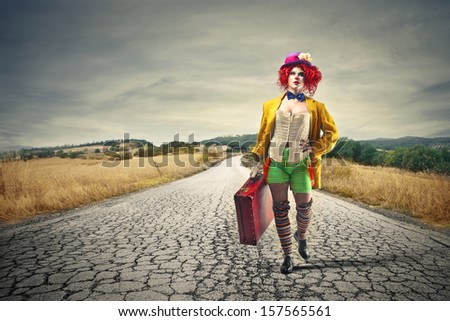 beautiful clown walking on a desert road with a vintage suitcase - stock photo