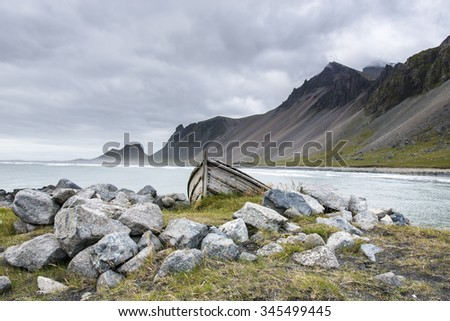 Beautiful coast Stokksnes with view to Atlantic ocean and mountains. Old fisherman boat. East of Iceland.