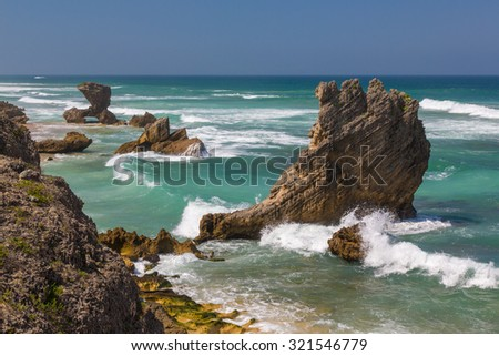 Beautiful coastline with rock formations at the coast at Kenton on Sea in South Africa - stock photo