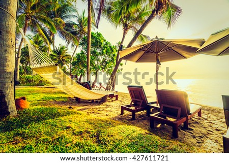 Beautiful coconut palm tree on the beach and sea with umbrella and chair on sunrise time - Vintage Filter - stock photo