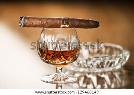 Beautiful cognac with cuban cigar close up shoot - stock photo