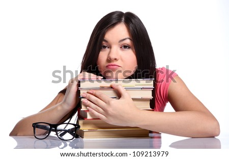 Beautiful college girl sitting near the glasses and holding books - stock photo