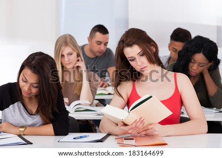 Beautiful college student reading book at desk in classroom - stock photo