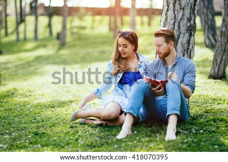 Beautiful college students flirting in park while studying