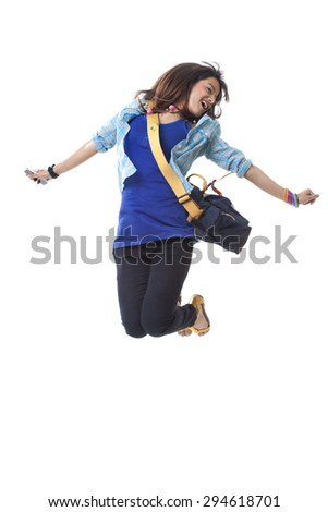 Beautiful college woman jumping while listening music over white background - stock photo