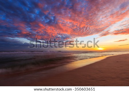 Beautiful colored clouds over the ocean at the beach at sunset - stock photo