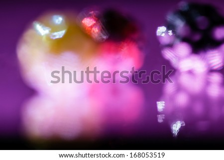 Beautiful, colored game of lights and reflexions on dark background