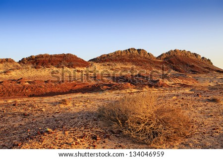 Beautiful colored rocks in the sand dunes in the middle of the desert in Oman on Route 35 - the 'Dunes highway' - stock photo