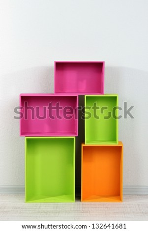 Beautiful colorful crates as shelves standing in room - stock photo