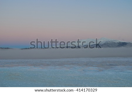 beautiful colorful dawn sky over frozen sea ice and thick ice fog - stock photo