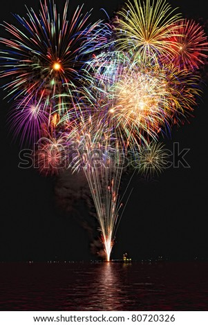 Beautiful colorful fireworks with night sky and lake reflections - stock photo