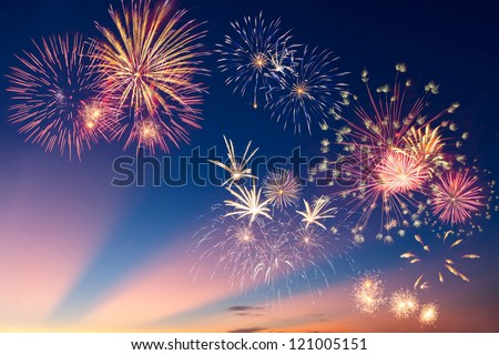 Beautiful colorful holiday fireworks in the evening sky with majestic clouds,  long exposure - stock photo