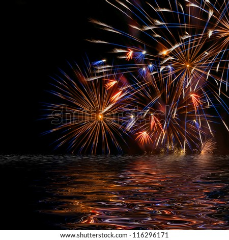 Beautiful colorful holiday fireworks with reflection on the black sky background, close-up, long exposure - stock photo