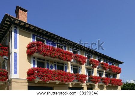 Beautiful colorful house in Navarra with red flowers on balcony