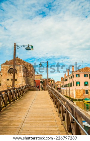 Beautiful colorful image of a street (Fondamenta Sant'Anna) in Venice with a bridge, old houses, lanterns, and cloudy sky above. - stock photo