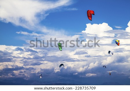 Beautiful colorful kites floating the sky. Water ski in Greece. Kite-surfing.
