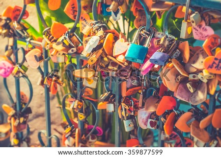 Beautiful colorful padlock surrounded by old keys on a steel fence background, Selective focus - Vintage effect style pictures - stock photo