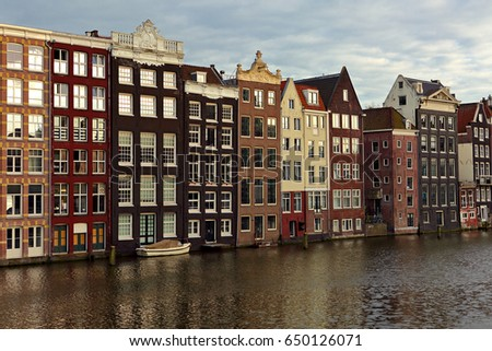 Beautiful colorful panorama view of old Amsterdam buildings near the river under blue sky in dusk light