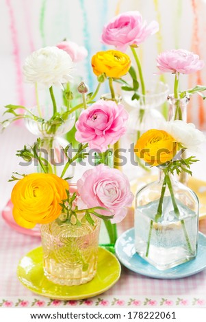 Beautiful colorful ranunculus in  glass bottles - stock photo