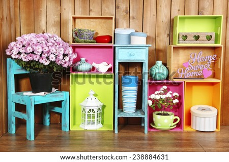 Beautiful colorful shelves with different home related objects on wooden wall background - stock photo