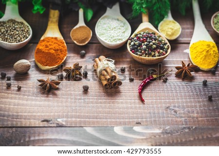 Beautiful colorful spices in poons and bowls with lettuce, dill and Basil on an old wooden brown table. Free space for your text