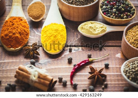 Beautiful colorful spices in wooden spoons and bowls on an old brown table.