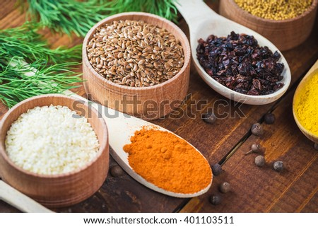 Beautiful colorful spices in wooden spoons and bowls on an old brown table with green dill