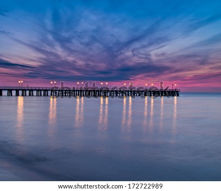 Beautiful colorful Sunrise on the pier at the seaside, Gdynia Orlowo, Poland. Long exposure photography  - stock photo