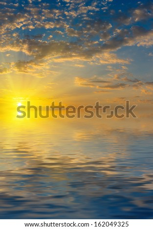 Beautiful colorful sunrise with rays of the sun above the sea - stock photo