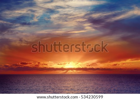 Beautiful colorful sunset at the sea with dramatic clouds and sun shining. Beauty world natural outdoors travel background.