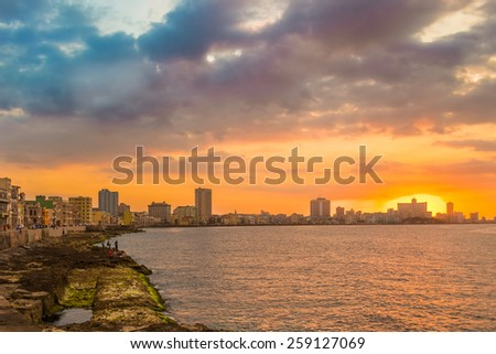 Beautiful colorful sunset in Havana with a view of the ocean and the city skyline - stock photo