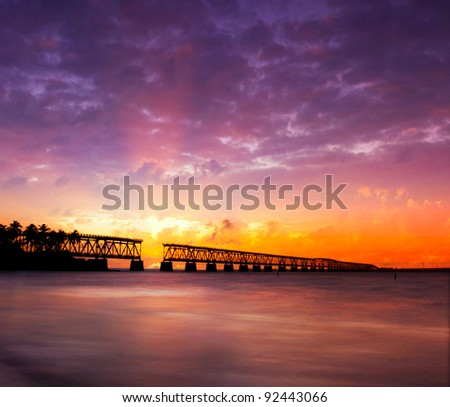 Beautiful colorful sunset or sunrise with broken bridge and sun rays spreading through purple clouds. Taken at Bahia Honda state park in the Florida Keys, near famous tourist destination of Key West. - stock photo