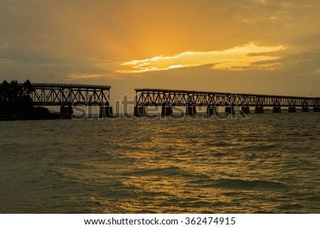 Beautiful colorful sunset or sunrise with old broken bridge and sun rays spreading through purple clouds.  Florida Keys. - stock photo