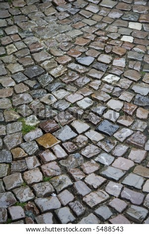 Beautiful colours of the cobblestones after rain - stock photo