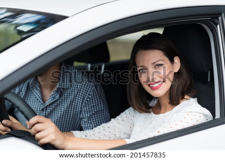 Beautiful competent female driver looking out of the window of the car with a lovely warm smile as she drives along with a male passenger - stock photo